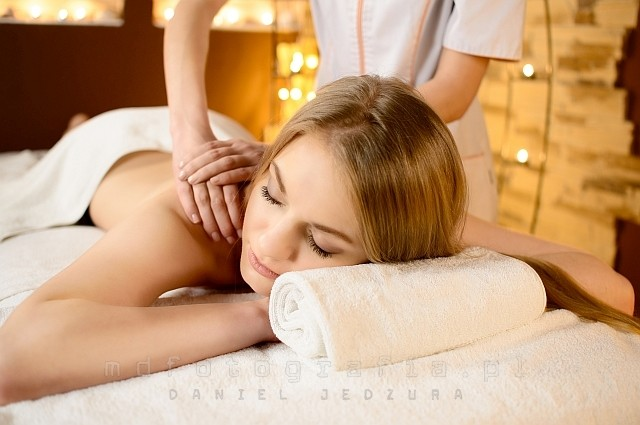 Young beautiful woman lying on a massage table and is being massaged